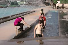 Niños jugando en una fuente del paseo